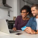 Couple using laptop to research secured vs unsecured credit cards