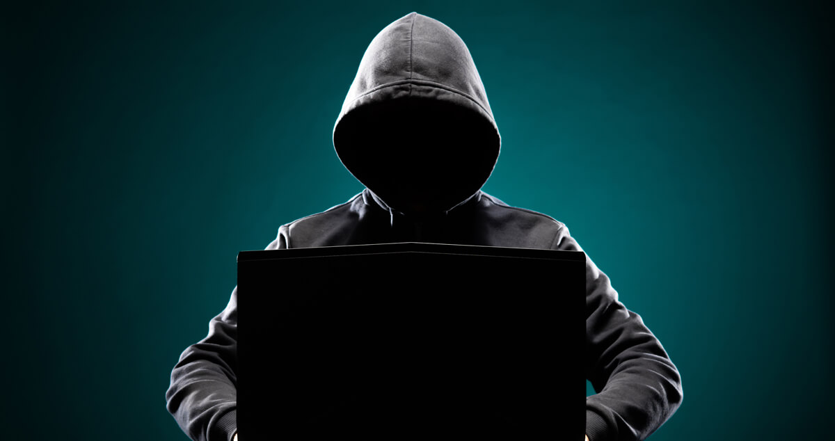 Man sitting in the shadows behind a computer depicting an identity thief