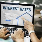 a couple looks at interest rates online to determine if they should refinance their mortgage