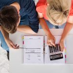 an overhead shot of a couple with a calculator and paperwork for refinancing their mortgage