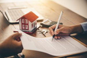 a women signs to refinance her mortgage