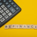 a calculator sitting on a yellow background with the word refinance spelled in block letters
