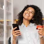 a young woman smiling about getting her first credit card with no credit, holding her cell phone in one hand and her card in the other