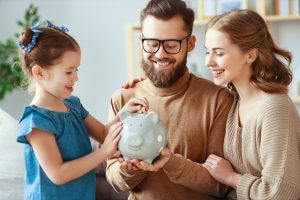 parents teaching their child good financial habits by saving money in a piggy bank