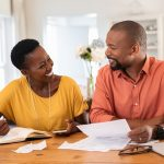 A happy African American couple review bills, pleased that automatic payments have kept their accounts up to date.