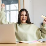 a young woman excitedly holding the no credit credit card she was approved for