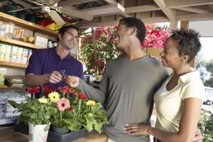 An African American couple uses a credit card to purchase flowers.